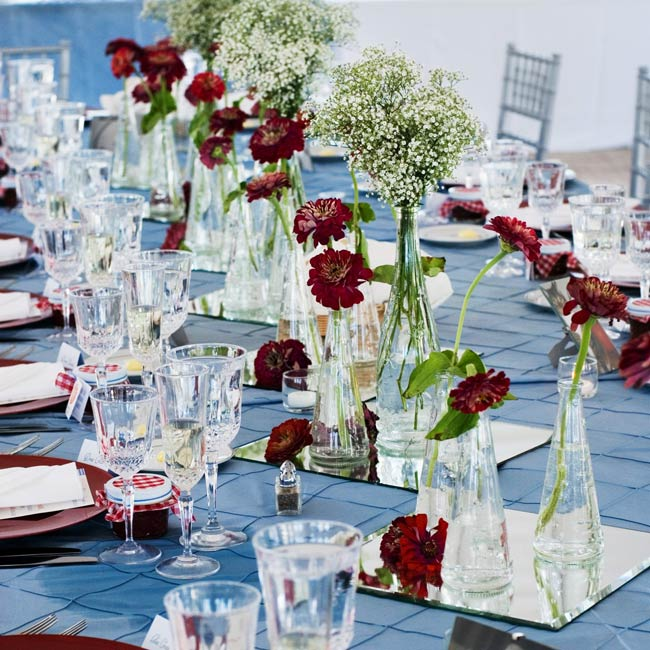 A row of square mirrors topped with baby's breath and zinnias highlighted the length of each banquet-style table. Blue, pintuck linens worked in the other color in the scheme, while photos of the couple's cats served as the backdrop for the table numbers.