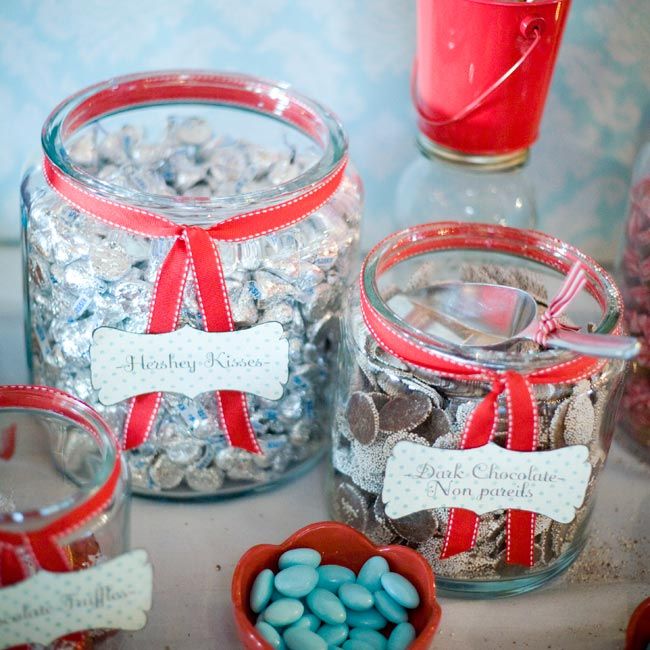 "At each setting, guests found a small jar filled with jellybeans and a note encouraging them to visit the candy bar. The candy bar offerings included dark chocolate nonpareils, chocolate ""wedding kisses"" and rock-candy lollipops."