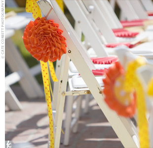 Orange, red, and yellow paper fans and a ceremony program were placed on each guest's chair. To create a splash of color, paper pinwheels lined the aisles, and yellow and orange polka-dot ribbons were tied to the backs of the chairs.