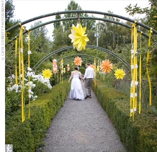 After the ceremony, guests walked to a garden area for the cocktail hour. Large paper flowers and escort cards hung with yellow ribbon decorated the space.