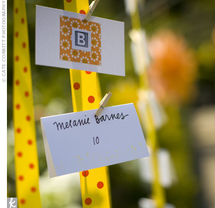 The DIY escort cards were attached to yellow and orange polka-dotted ribbon with tiny wooden clothespins.