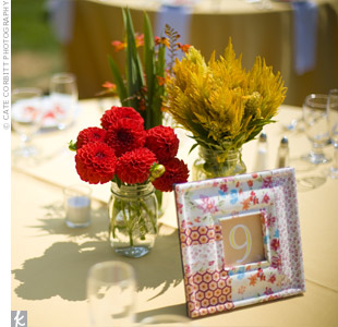 The centerpieces were mason jars in various sizes, each holding a different type of flower. Fabric-covered picture frames displayed the table numbers.