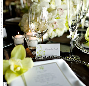 Coordinating escort cards directed guests to their seats. The place settings were adorned with a menu and a single green orchid.