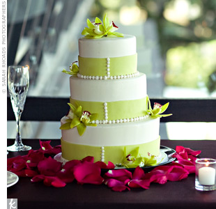 "Set atop a chocolate-brown table, the white buttercream-frosted confection was decorated with green ribbon. Delicate pearl piping and green cymbidium orchids adorned the cake, while a border of hot pink rose petals added a punch of color. The two etched crystal flutes served as the couple's ""something borrowed"" from the bride's mother."