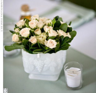 Milk-glass bowls filled with the same type of blooms in the bridesmaid bouquets topped satin runners. Votive candles filled the gaps between each arrangement.