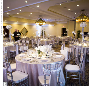 Guests sat in silver chiavari chairs at reception tables that were topped with silver linens, which coordinated nicely with the metallic wedding color palette.