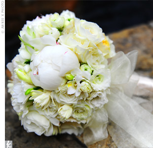 Melanie carried a rounded bouquet of white and cream flowers: open garden and Ecuadorian roses, peonies, ranunculus, freesias, lisianthus, and sweet peas. The stems were wrapped and tied with ivory organza ribbon.