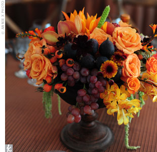 The table centerpieces complemented the elegant wine country atmosphere and featured open orange roses, copper-colored echinacea pods, Sunkist orchids, lime cymbidiums, apricot Macarena roses, chocolate cosmos, and orange dahlias with fresh grapes, cracked open pomegranates, figs, and amaranthus.