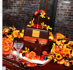 Melanie and Drew's square, monogrammed wedding cake was covered in a chocolate glaze and made with candy bar and Baileys Irish Cream filling. It was decorated with fresh fruit, harvest flowers, and edible sugar made copper bands.