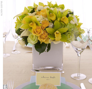 Mix up textures for place settings that guests will remember. Top a frosted, colored plate with a shimmery place card holder. A coating of spray mount and a roll in glitter help this lemon sparkle. Keep the place card simple, but let the centerpiece shine. A bold arrangement of cymbidium orchids, roses, calla lilies and ranunculus in a stark-white, ...