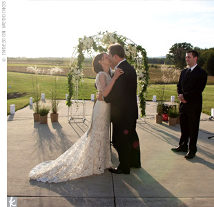 The couple exchanged traditional vows beneath a white iron arbor set up on the concrete apron outside of the hanger. As a thank-you, they gave the arbor to their officiant, Thor's close family friend, to put in his garden.