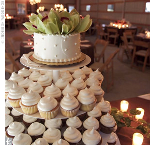 Three tiers of carrot cake, vanilla and chocolate cupcakes with buttercream gave height to a smaller bride-and-groom cake decorated with cymbidium orchids.