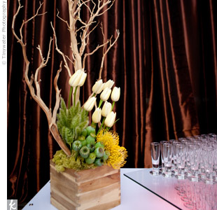 An organic arrangment of tulips, pincusion protea, seed pods, and driftwood created a dramatic centerpiece.