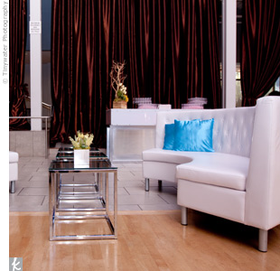 Mod white couches were positioned alongside chrome and glass tables.