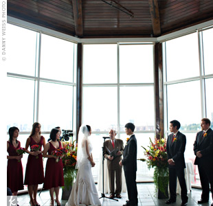 Floor-to-ceiling windows that looked out onto the Hudson River provided the backdrop for the ceremony. To personalize the space, the couple added brightly colored altar arrangements of lilies, Gerbera daisies, and loads of greenery.