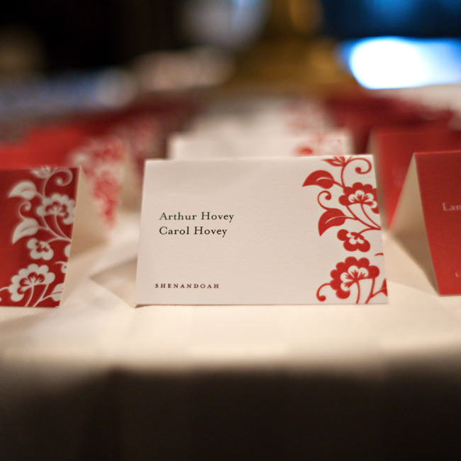 An Asian floral motif decorated the sides of the tented escort cards. The background color and accent color alternated from row to row in the display.