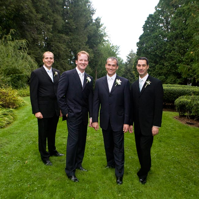 Purple pinstripes and dendrobium orchid boutonnieres distinguished the grooms from their groomsmen, who also wore navy suits, but with freesia boutonnieres.