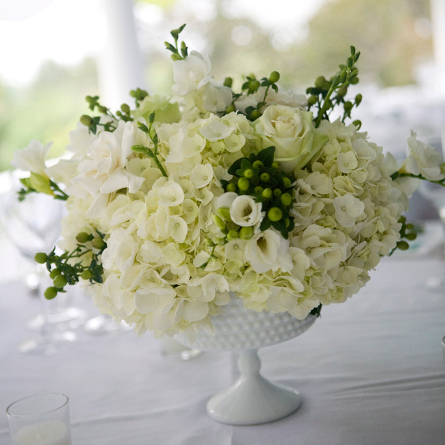Instead of generic glass vases, the couple used authentically vintage hobnail milk-glass compotes for their rose, hydrangea, freesia, gardenia, and hypericum berry centerpieces.