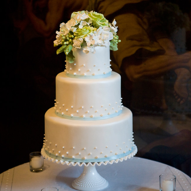 The dotted design of the dessert mimicked the pattern of the centerpiece vessels. Icing ribbons and a dramatic sugar flower topper worked in the palette.