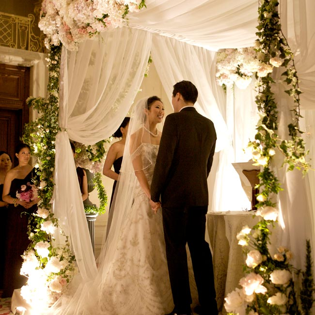 A dramatic canopy covered in hydrangeas, peonies, roses, ivy and smilax kept the focus on the action at the ceremony. Uplighting called attention to the lush flowers.