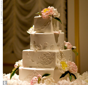 Taking its cue from the bride's intricate gown, the fondant-iced cake had lace designs and silver and pearl accents. Because it wouldn't be Winnie's wedding cake without peonies, sugar versions of her favorite flower decorated the tiers.