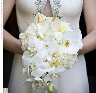 Angelas all-white, cascading bouquet of phalaenopsis and cattleya orchids, gardenias, anthurium, and anemones was wrapped in gray velvet ribbon.