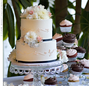 Angela and Michael's two-tiered cake was covered with white frosting and decorated with fresh flowers. Pink piping added a vintage look to the tiers. The couple also ordered a selection of cupcakes frosted with strawberry and chocolate.