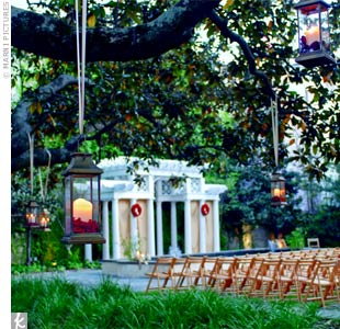 Guests sat in wooden garden chairs beneath a magnolia tree strung with glass lanterns filled with ivory pillar candles and rose petals.