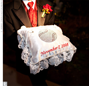 Josh's mom, a sewing instructor, hand-made the satin ring pillow herself. She embroidered the couple's names and wedding date in red and bedazzled it with a baseball.