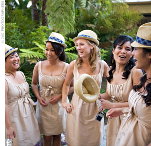 To match the wedding colors, Therese's bridesmaids wore tan, knee-length dresses. For the entrance into the reception, the girls wore the guys' straw fedora hats, and the guys carried the girls' bouquets.