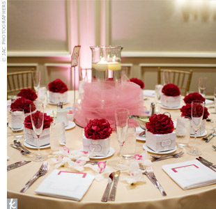 As an alternative to traditional floral arrangements, the centerpieces were large hurricane vases filled with water and floating candles. Pink tulle was wrapped around the vases for a pop of color. Handmade paper flowers atop the favor boxes also decorated the tables.