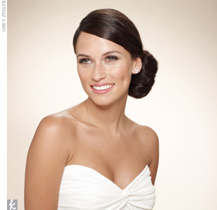 """It's no surprise these knots are all over the bridal runways. A bun is the perfect place to pop in flowers or sparkly hairpins.    How to Get the Look: Step 1: Use a 1"""" curling iron to add texture to straight hair. The curls will help keep your hair looking loose. Step 2: Find your nautral part and pull your hair into a love side ponytail behi ..."""