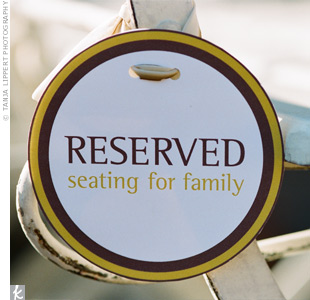 To save seats for their VIPs, Lisa and Benjamin tied round reserved signs to front-row chairs at their outdoor ceremony.