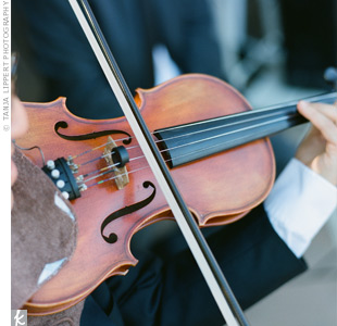 "A sophisticated duo, a violinist and a pianist, played the traditional ceremony favorites ""Air on a G String"" and ""Canon in D Major"" during Lisa and Benjamin's elegant ceremony."