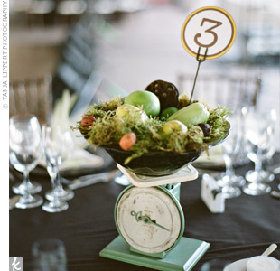 Kitchen scales with fresh fruit, dried lotus pods and Spanish moss started conversations at the guests' tables. Round table numbers matched the rest of the circular details.