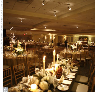 The long tables were covered with gold linens and moss-green velvet runners. Winter-white blooms, evergreen boughs, birch logs, lanterns, silver candlesticks and glass ornaments ran down the center of every table.