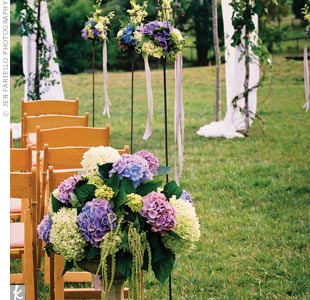Since the scenery was so lush, the couple kept their décor simple with a fabric canopy, candle stakes and pedestal vases filled with hanging amaranthus and hydrangeas.
