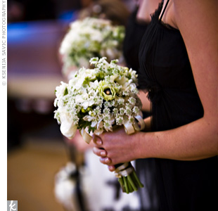 The bridesmaids carried bouquets of anemones, Queen Annes lace, and stock accented with Swarovski crystals and sprayed with iridescent glitter.