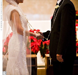 "During their ceremony, Julie and Vince wore an oversized rosary, called a ""lasso,"" as a Latin Catholic tradition. Vince's father's side of the family had passed it along to them as a gift."