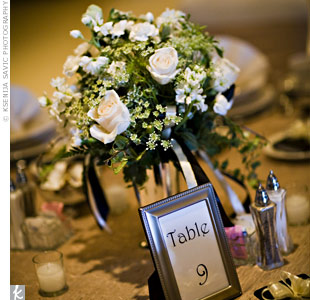 The couple had two requirements for the centerpieces: They had to look traditional and couldn't obstruct the view from the opposite side of the table. Their florist went with anemones, hydrangeas, Vendela roses, Queen Anne's lace, white lacy ivy, and variegated pittosporum. Black, ivory, and gold ribbon hung from all the arrangements, which were fi ...