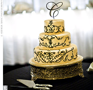 "To match their color palette, Julie and Vince chose a shimmery gold, three-tiered cake and a cursive ""C"" cake topper."