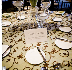 Green satin tablecloths and brown, floral overlays covered the round reception tables while brown satin tablecloths covered the square ones. Each table was numbered and also named after a place special to the couple, like cities they've traveled to and where they'd grown up.