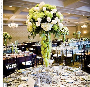 To mix things up, several different centerpieces decorated the reception tables. Some were tall, filled with pears, and topped with full arrangements of ivory roses, green hydrangeas, and chocolate cosmos.