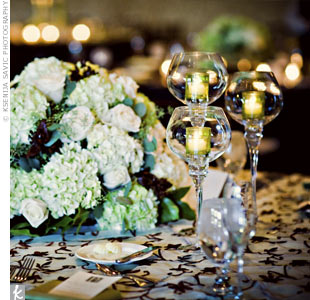 The lower centerpieces were arranged with ivory roses, green hydrangeas, and chocolate cosmos.
