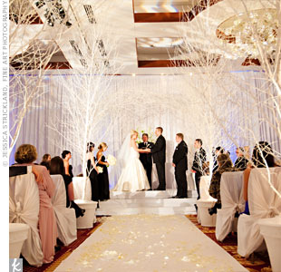 Susan and Paul brought in 14 trees, that they had spray-painted white, to decorate for a crisp, clean, winter wonderland ceremony. The flower girls, dubbed snow fairies, sprinkled the aisle with white rose petals and snowflakes.