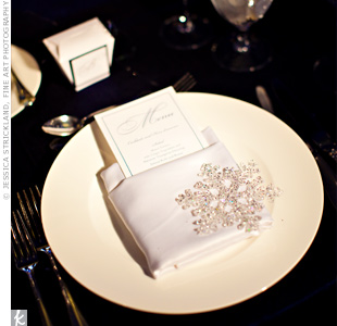 A crystal snowflake decorated each table setting. The white plates, napkins, and menu cards popped against the navy blue tablecloths. At their place settings, guests also found custom-made blue fortune cookies -- a nod to Paul's proposal.