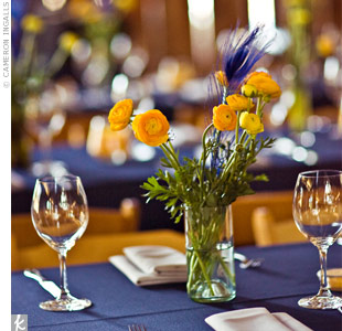 Simple arrangements of yellow ranunculus accented with peacock feathers popped against the navy tablecloths. Tara and Mitch made the vases out of wine bottles that they had collected in the months before the wedding. They used a glass cutter to create the vases in different sizes and colors.