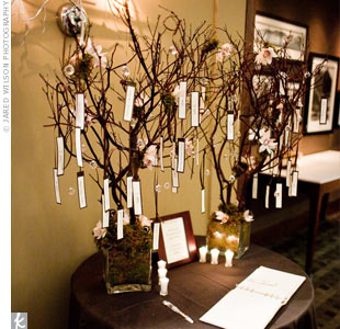 Rectangular escort cards hung by ribbon from two Manzanita trees decorated with orchids.