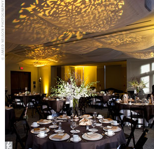 The couple rented champagne-hued napkins to coordinate with the hotel's brown linens and chairs. Floral-patterned uplighting decorated the ceiling.