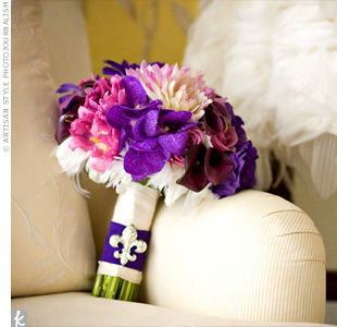 Colleen's purple and pink bouquet was made up of mini calla lilies, phalaenopsis orchids, tulips, and mums, and accented with white pheasant feathers. The stems were wrapped in white ribbon and the same purple fabric from Colleen's dress. She added a fleur-de-lis pin for some sparkle.